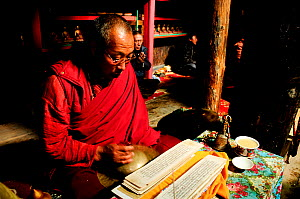 Bhojo Buddhist monastery with monk reading sacred text (3.500m), Manang. Annapurna Conservation Area, Himalayas, Nepal, October 2009.  -  Enrique Lopez-Tapia