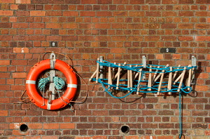Safety equipment mounted on wall at Seacombe, Merseyside, England, August 2012. - Norma Brazendale