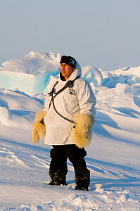 Man wearing traditional polar bearskin gloves stands on pack ice over the Chukchi Sea. Offshore from Barrow, Arctic coast of Alaska, spring, May 2012. - Steven Kazlowski