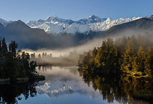 RF- Morning mist and reflections on Lake Matheson with Aoraki / Mount Cook (right; 3754m) and Mount Tasman (left; 3498m). Fox Glacier, Westland National Park, South Island, New Zealand. September, 200... - Andy Trowbridge