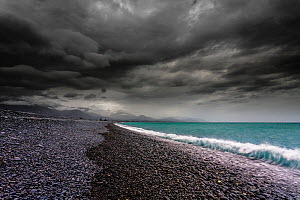 Moody sky over stoney beach, with mountains just visible in the background, Kaikoura, Canterbury, South Island, New Zealand. September, 2006.  -  Andy Trowbridge