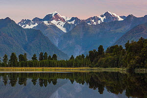 Late evening light on the Souttern Alps being perfectly relected in the calm waters of Lake Matheson. New Zealand's highest mountain, Mount Cook or Aoraki (3754m) is tho the right, and Mount Tasman (3... - Andy Trowbridge