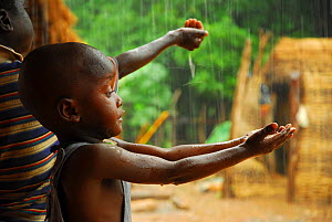 A bassari child holding out hands to collect rainwater, Bassari country,  east Senegal. This area became a UNESCO World Heritage site in 2012, for cultural landscape and traditions kept by the the Bas...  -  Enrique Lopez-Tapia