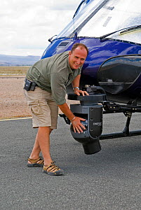 Cameraman Martyn Colbeck with mounted Cineflex camera on helicopter. Amboseli, Kenya. December 2007. Taken on location for BBC tv series 'Life' - Martha Holmes