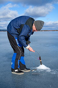 Ice fishing on a freshwater lake, Sweden, April 2008 - Peter Cairns