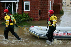 Members of north wales fire service with boat to rescue people affected by flooding of newly built housing in the Glasdir estate, Ruthin, Vale of Clwyd, Denbighshire, Wales, UK.  This is an area at ri...  -  David Woodfall