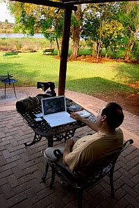 Nature photographer Oriol Alamany editing photographs on his laptop at Lower Sabie Camp, Kruger National Park, Transvaal, South Africa, September.  -  Oriol Alamany