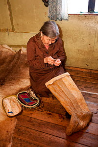 Yalena, an elderly Selkup woman, sewing a pair of traditional reindeer skin boots, Krasnoselkup, Yamal, Western Siberia, Russia 2012 - Bryan and Cherry Alexander