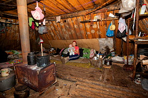 Lena Kuboleva, a young Selkup woman, with her daughter Violetta, inside a 'Poymot', (traditional Selkup turf winter hut), at a winter hunting camp in the forest near Ratta, Krasnoselkup, Yamal, Wester... - Bryan and Cherry Alexander