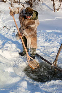 Gennadiy Kubolev, using a traditional Selkup shovel to remove pieces of ice from the water while checking a fishing net in a frozen river,  Krasnoselkup, Yamal, Western Siberia, Russia 2012 - Bryan and Cherry Alexander