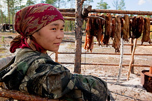Rita Markova, a young Selkup woman, at a summer camp in the taiga, with animal pelts drying behind her, Krasnoselkup, Yamal, Western Siberia, Russia - Bryan and Cherry Alexander