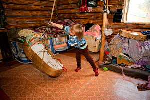Anastasia, a five year old Selkup girl, rocks the cradle of her baby cousin at a summer camp in the forest, Krasnoselkup, Yamal, Western Siberia, Russia. - Bryan and Cherry Alexander