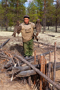 Gennadiy Kubolev, a Selkup hunter, holds two Capercaille he has caught in a 'Chang' (traditional deadfall trap), in the forest, Krasnoselkup, Yamal, Western Siberia, Russia - Bryan and Cherry Alexander
