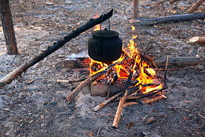A kettle hangs over an open fire to boil at a Selkup camp in the forest, Krasnoselkup, Yamal, Western Siberia, Russia  -  Bryan and Cherry Alexander