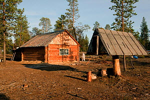 Log cabin at a Selkup summer camp in the forest with a traditional raised wooden food storage hut (to avoid rodent problem) Krasnoselkup, Yamal, Western Siberia, Russia - Bryan and Cherry Alexander