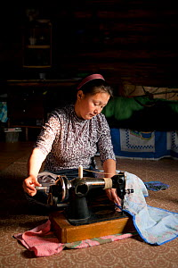 Lena Kuboleva, a young Selkup woman, using a sewing machine on the floor of her family's log cabin, Krasnoselkup, Yamal, Western Siberia, Russia - Bryan and Cherry Alexander