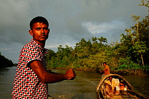 Men on a wooden boat who use smooth-coated otters (Lutra perspicillata) for traditional fishing practices,  the Sundarbans National Park, the largest mangrove swamp in the world. Bangladesh. UNESCO Wo... - Enrique Lopez-Tapia