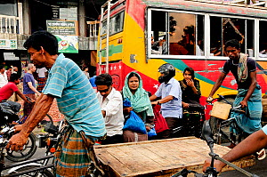 A busy street with people walking,  and cycling through Dhaka, Bangladesh, June 2012. - Enrique Lopez-Tapia