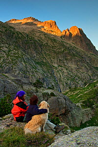 Two women hikers sitting with a Montana de los Pirineos domestic dog  at sunset watching the Remuae Valley, Parque Natural Posets-Maladeta Ribagorza, Pyrenees Huesca, Aragon, Spain. Model released. - Oriol Alamany