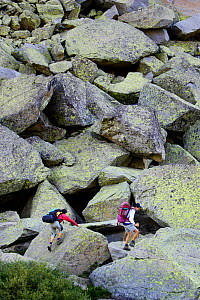 Hikers crossing  scree  along the 'Carros de foc' trail, Boi valley, Aiguestortes i Estany de Sant Maurici National Park, Pyrenees, Catalonia, Spain. No release available. - Oriol Alamany
