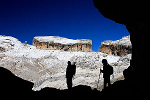 Two hikers silhouetted in Casteret ice cave with Brecha de Rolando / Roland's breach in the background, Ordesa and Monte Perdido National Park, Pyrenees, Aragon, Spain - Oriol Alamany