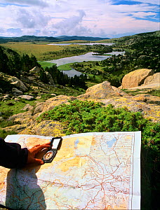 Hiker orienting a map with a compass in Estanys de Les Bouillouses, Pyrenees Catalanes Natural Park,  Languedoc-Roussillon, France - Oriol Alamany