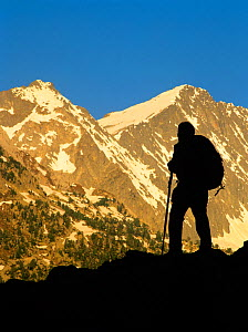 Woman hiker silhouetted at sunrise in Conangles valley, Aran Valley, Pyrenees, Catalonia, Spain. Model released - Oriol Alamany