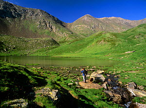 Hiker  with dog on the shores of Estany de Filia� alpine lake in Vall Fosca, Pyrenees, Pallars Jussa, Catalonia, Spain. Model released - Oriol Alamany