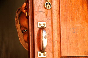 Girl peeping out from behind door,  Stone Town, Zanzibar, Tanzania. No release available.  -  Enrique Lopez-Tapia