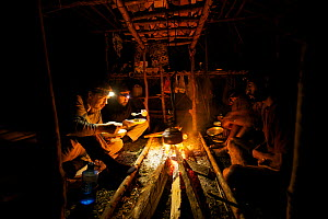 Camp life at Sombom Camp in the Saruwaged Range, Huon Peninsula. Photographer Tim Laman (front left) and ornithologist Ed Scholes (back left), and Papua New Guinean field assistants warm up at the fir...  -  Tim Laman/Nat Geo Image Collection