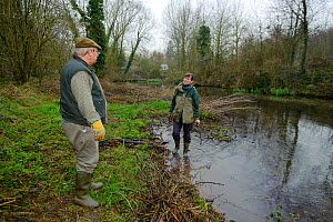 A member of staff from the Wildwood Trust, talks to landowner, during conservation efforts to improve water vole habitat on a stream by cutting trees to allow growth of bankside vegetation, East Malli... - Terry Whittaker / 2020VISION