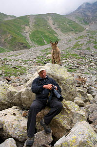Photographer Patricio Robles Gil reviewing his work with a West Caucasian tur (Capra caucasica) behind him looking on. Kabardino-Balkarsky Nature Reserve, Caucasus Region of Russia. - Igor Shpilenok