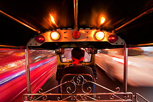 Tuk Tuk or auto rickshaw in motion at night, Bangkok, Thailand, 2010. Model released. - Gavin Hellier