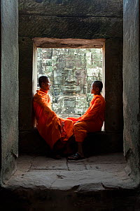 Two buddhist monks relaxing in the Bayon Temple, Angkor Wat, Siem Reap, Cambodia 2010. Model released.  -  Gavin Hellier