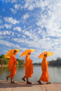 Three Monks with parasols by the moat surrounding Angkor Wat Temple complex, Siem Reap, Cambodia, 2010  -  Gavin Hellier