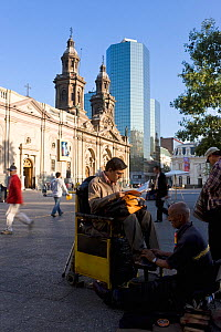 Shoe shining work infront of Cathedral Metropolitana and modern office building in Plaza de Armas, Santiago, Chile, 2008 - Gavin Hellier