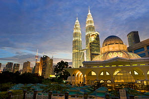 Mosque in the KLCC city park grounds at the base of Petronas Towers at night - 88 storey steel clad twin towers with a height of 451.9 metres - the iconic symbol of Kuala Lumpar, both illuminated at n...  -  Gavin Hellier