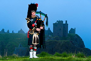 Skirlie McPiper wearing traditional dress playing bagpipes at Dunnotar Castle. Scotland, April 2011. - Niall Benvie