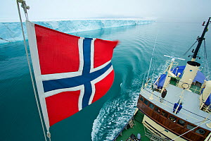 Norwegian flag set on M/S Stockholm and ice front of Brasvellbreen seen from crow's nest, Austfonna, Nordaustlandet, Svalbard, Norway, July 2012 - Florian Möllers