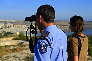 Fiona Burrows from BirdLife Malta and ALE (Administrative Law Enforcement) Officer monitoring illegal Turtle Dove (Streptopelia turtur) trappers on hillside, during BirdLife Malta Spring Watch Camp,...  -  David Tipling