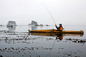 Fly fishing from a kayak in the Straits of Juan De Fuca near Sail and Seal Rocks. Washington, USA, August. Model released. - Kirkendall-Spring