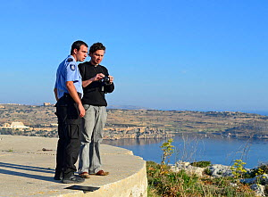 Nick Barbara and ALE Police officer reviewing video footage of illegal Turtle Dove trapping during BirdLife Malta Springwatch Camp April 2013  -  David Tipling