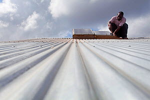Technician fixing solar panel on a corrugated iron rooftop, Miono region, Tanzania.  -  Tom Gilks