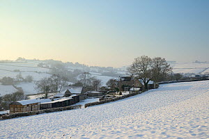 Snow covered ploughed field, farm buildings and hillside pastureland in late afternoon light, Tadwick, Bath and Northeast Somerset, UK, January 2013  -  Nick Upton