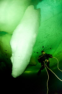 Scuba diver under ice next to ice formation, Arctic circle Dive Center, White Sea, Karelia, northern Russia, March 2010  -  Franco Banfi