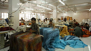 Timelapse of factory workers using sewing machines in a garment factory, Rajasthan, India, 2011. - Gavin Hellier