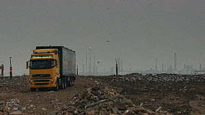 Lorry driving across a landfill site with a gas flare in the background, Pitsea, Essex, England, UK, November 2011.  -  Will  Bolton / 2020VISION