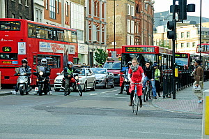Cyclist and motor cyclist pulling away from traffic light during the rush hour, Angel, London Borough of Islington, England, UK, May 2009 - Pat  Tuson
