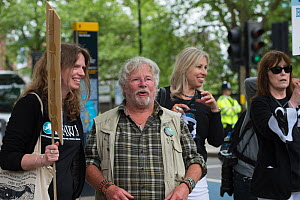 Naturalist and TV presenter Bill Oddie talking to a protestor holding a sign, at anti badger cull march, London 1st June 2013. - Terry Whittaker