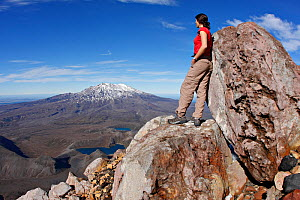 Woman on top of Mount Ngauruhoe ('Mt. Doom' from the 'Lord of the Rings' movies) looking out  Volcanic scenery along the Tongariro Alpine Crossing, with Mount Ruapehu in the distance.  North Island, N...  -  Brandon Cole